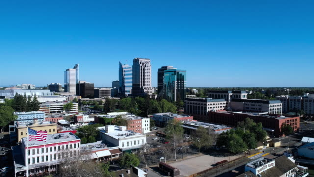 Remote view to Sacramento Downtown over Old Sacramento Waterfront District. Aerial drone video with the forward camera motion. - vídeo