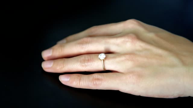 vídeos de stock e filmes b-roll de remove engagement wedding ring from ring finger. concept of divorce, marriage problem. - remover