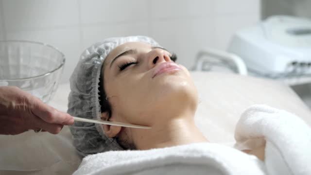 vídeos y material grabado en eventos de stock de retirar con espátula la espuma de la cara. mujer bonita joven recibiendo tratamientos en salones de belleza. limpieza usando espuma facial. - dermatología