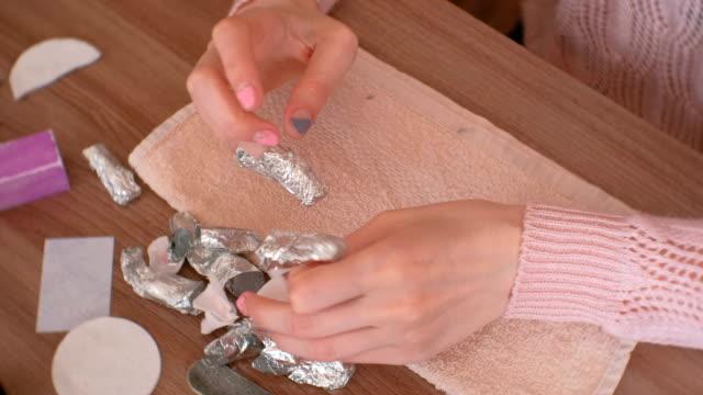 ta bort gel polish från naglar. kvinnan tar folien av fingrarna. och ta bort shellack naglar med pusher. närbild hand. - nagellack bildbanksvideor och videomaterial från bakom kulisserna