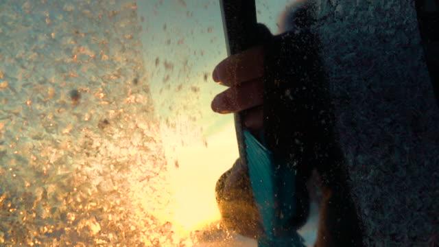 vidéos et rushes de slow motion macro: enlever fleurs glacées d'une fenêtre de voiture gelée matin d'hiver - pare brise