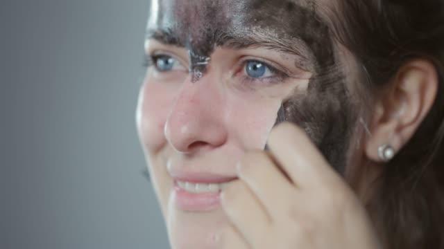 vídeos de stock, filmes e b-roll de removendo o descasque fora a máscara de rosto - descascado
