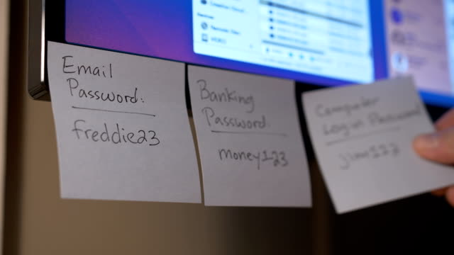 Removing Sticky Notes with Password Reminders from Monitor A person removes Post-It password reminders from a computer monitor. password stock videos & royalty-free footage