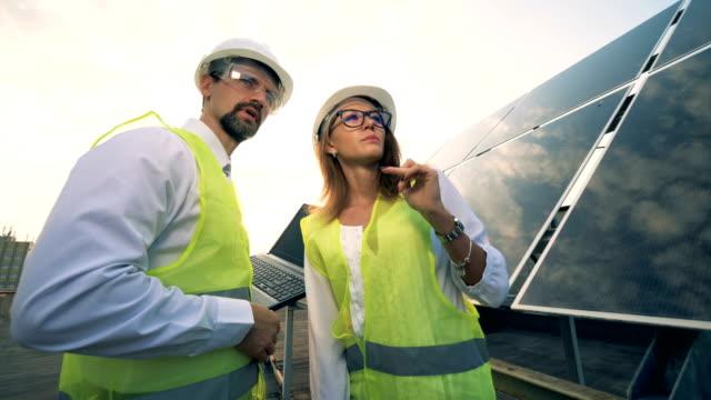 Renewable energy concept. Energetics workers, electrical engineer near solar panel.