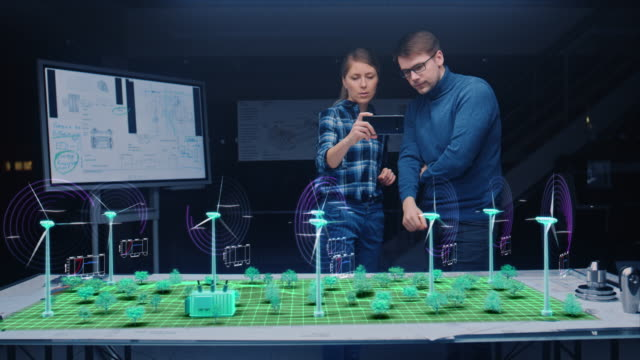 Renewable Energy Engineers Design 3D Wind Turbine Park Using Augmented Reality Hologram and Smartphone. Specialists Use Virtual Reality App to Work on Green Energy Environmental Power Production Renewable Energy Engineers Design 3D Wind Turbine Park Using Augmented Reality Hologram and Smartphone. Specialists Use Virtual Reality App to Work on Green Energy Environmental Power Production renewable energy stock videos & royalty-free footage
