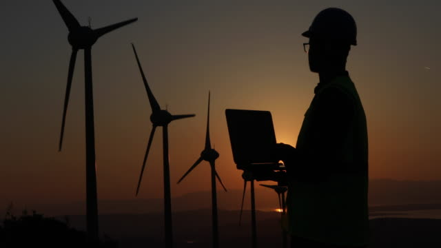 Renewable Energy Systems Engineering Silhouette of young male engineer holding laptop computer planning and working for the energy industry and standing beside a wind turbines farm power station at sunset time. izmir stock videos & royalty-free footage