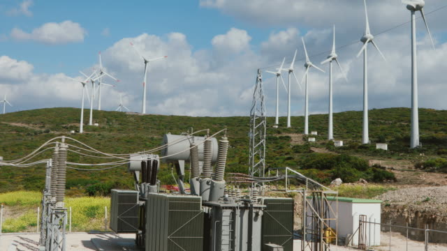 renewable green energy - power substation and wind turbines - sottostazione elettrica video stock e b–roll