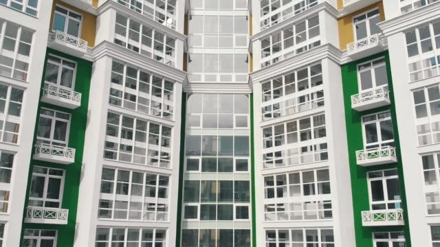 renovated multi-storey building of green white colors aerial video