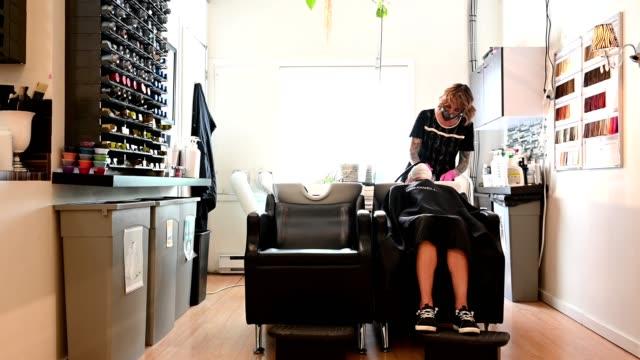 vídeos de stock e filmes b-roll de reopening a beauty salon with coronavirus safety measures - covid hair