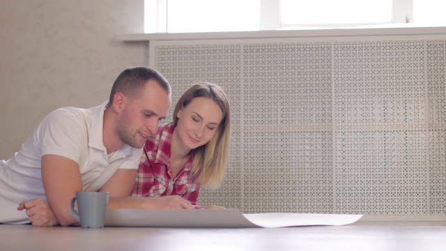 repair, building, renovation and home concept - smiling couple discussin blueprint at home video
