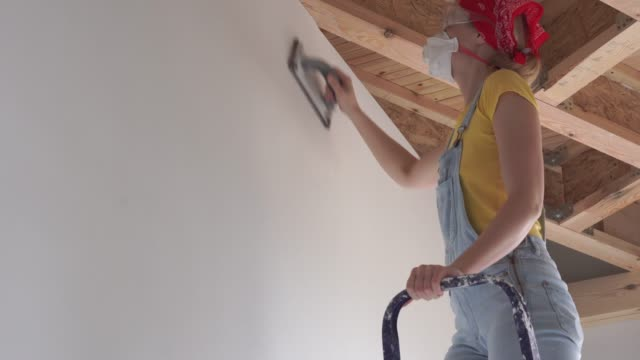 repair in the apartment - a young woman of European appearance makes repairs at home - wall surface polishing repair in the apartment - a young woman of European appearance makes repairs at home - wall surface polishing. house painter stock videos & royalty-free footage