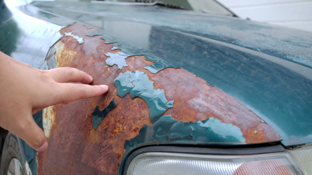 4K Repair man using his hand to touch the Rusting old cars, the paint falls off. The old green car in the off-color condition