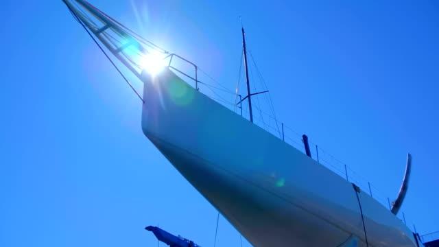 reparation av en stor vit yacht installerad på skepps vägen i hamnen - skrov bildbanksvideor och videomaterial från bakom kulisserna