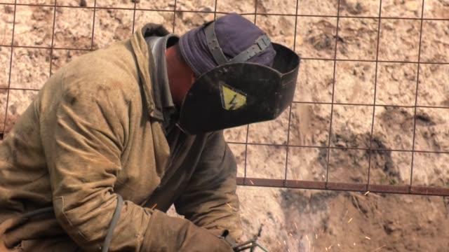 vídeos y material grabado en eventos de stock de reparación de la línea de suministro de calor. soldador de usar ropa de protección para la soldadura de construcción industrial agua y tubería de plomería de alcantarillado fuera de sitio. - tubería