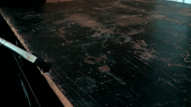 Repairing old black wooden furniture. Close-up of brush with black paint. video