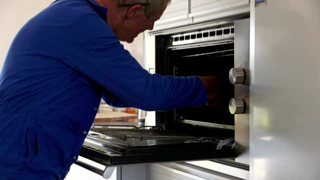 Repairman at Work A senior worker works on an oven as he fixes it with his tools. He is wearing blue overalls over a white tshirt. appliance stock videos & royalty-free footage