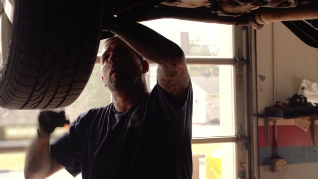 Repairman - auto mechanic, Caucasian White man with tattoos on hands, working in a car repair shop - fixing suspension of the car elevated on the lift.