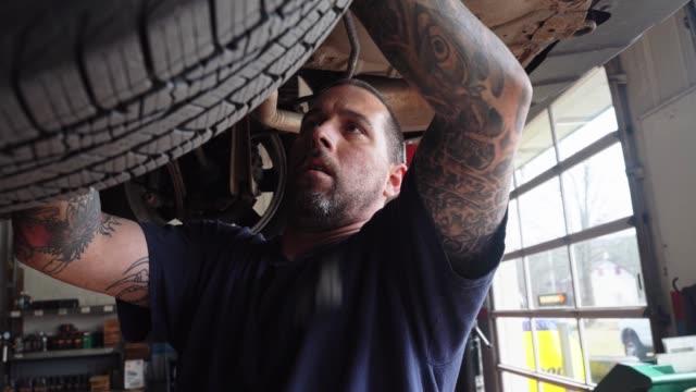 vidéos et rushes de réparateur - mécanicien automobile, homme blanc caucasien avec des tatouages sur les mains, travaillant dans un atelier de réparation de voiture - fixation de la suspension de la voiture élevée sur l'ascenseur. - vue en contre plongée verticale