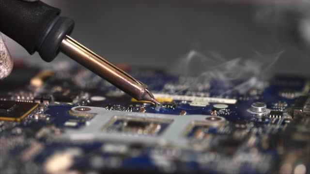 vídeos y material grabado en eventos de stock de reparador en guantes es la placa base de soldadura de dispositivo de computadora en el taller. - placa madre