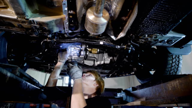 repairman of car workshop is standing under lifted automobile and examining details, checking backlash in a suspension repairman of car workshop is standing under lifted automobile and examining details, checking backlash in a suspension, lighting by lantern suspension bridge stock videos & royalty-free footage