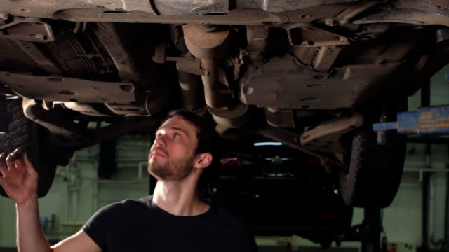 Repairman of Car Workshop Is Standing Under Lifted Automobile and Examining Details video