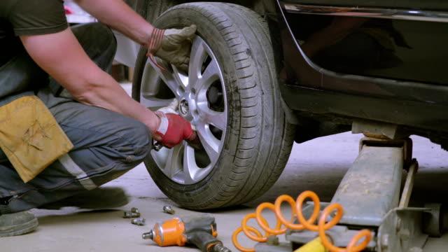 en reparatör att sätta på däcket på bilen - verkstad bildbanksvideor och videomaterial från bakom kulisserna