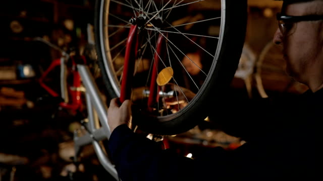Repairman repairing bicycle in workshop video