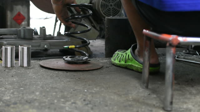 repairman working for welding car coil spring - molla video stock e b–roll
