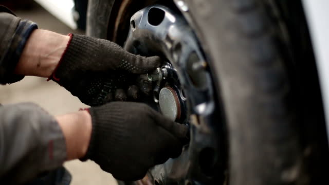 Replacement car tire at the service station. Slow motion video