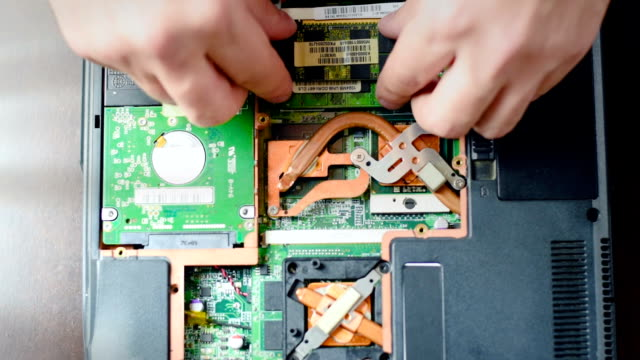Replacement of RAM in the laptop. The man turns off the main memory. Hands close up video