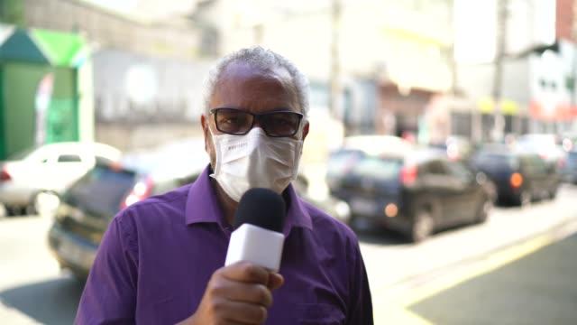 vidéos et rushes de homme de journaliste de tv utilisant un masque de visage parlant à la caméra d'enregistrement - interview