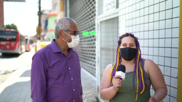 vidéos et rushes de journaliste de tv utilisant un masque de visage interviewant une femme à la rue - interview
