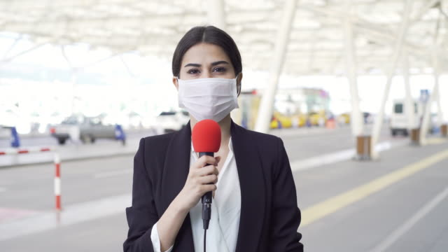 TV reporter wearing a mask