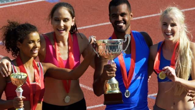 彼らを獲得した国民的スポーツ チームのファンのトロフィーを表示の代表者 - メダル点の映像素材/bロール