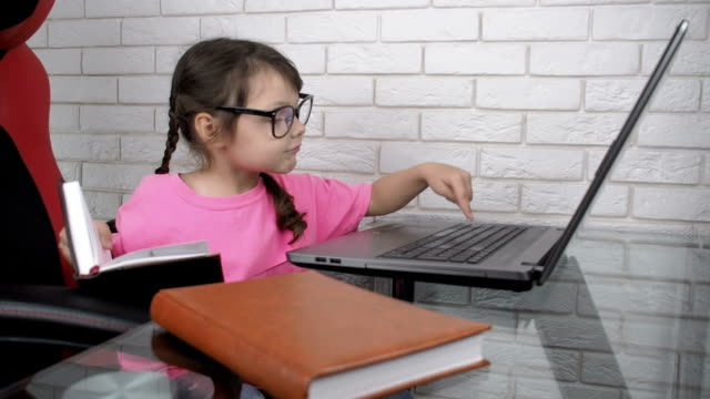 Reprinting. Child with glasses reprints text on keyboard with book. Reprinting. Child with glasses reprints text on keyboard with book. Girl is sitting at desk and looks carefully her book and then writes on laptop. pigtails stock videos & royalty-free footage