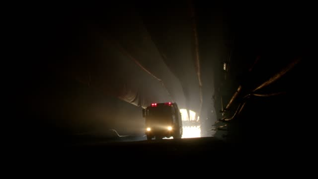 rescue truck driving into a dark construction tunnel - sottosuolo video stock e b–roll