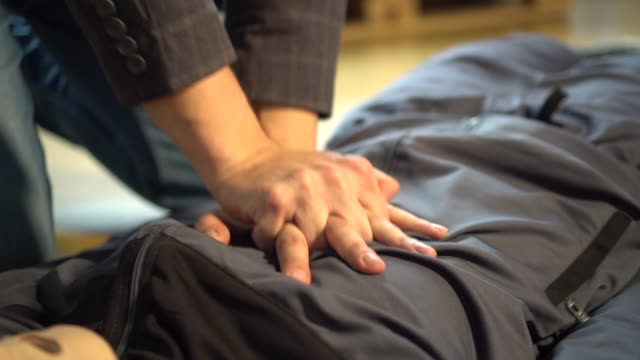 rescuer hands doing emergency cpr on heart attacked. first aid training. cpr cardiopulmonary resuscitation. - torace umano video stock e b–roll