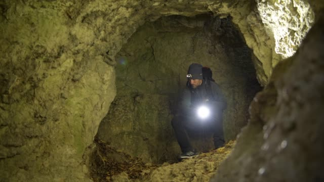rescuer with flashlight looking around in the deep cave. rescue mission. - кейвинг стоковые видео и кадры b-roll