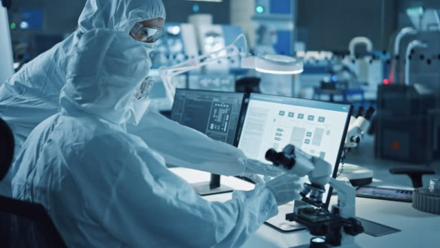 Research Factory Cleanroom: Engineer and Scientist Wearing Coveralls Talk and Work on Computer, Use Microscope to Inspect Motherboard Microprocessor, Develop Electronics for Medical Electronics