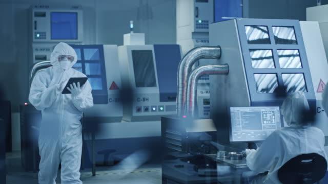 vídeos de stock, filmes e b-roll de sala de limpeza da fábrica de pesquisa: engenheiro usando macacão e máscara, andando através de workshopop usa tablet. em formação profissionais trabalham em máquinas cnc modernas de alta tecnologia - higiene