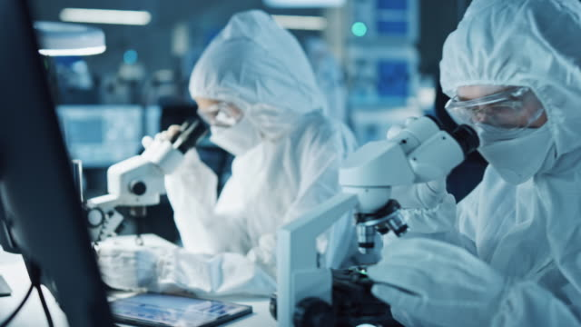 Research Factory Cleanroom: Engineers / Scientists wearing Coveralls and Gloves Use Microscopes to Inspect Motherboard Microprocessor Components, Developing High Tech Modern Electronics