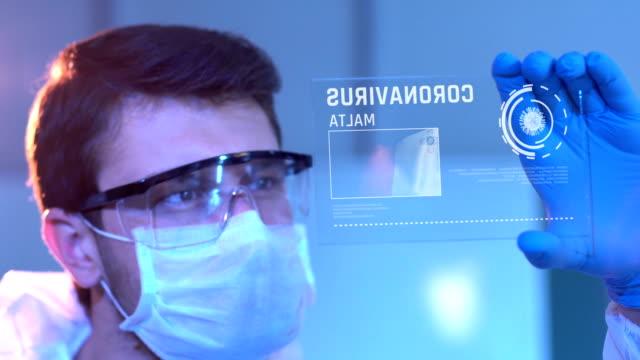 Researcher Looking at Coronavirus Results. Maltese Flag on Digital Screen in Laboratory