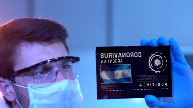 researcher looking at coronavirus results of argentina. argentinian flag on digital screen in laboratory - bandiera dell'argentina video stock e b–roll