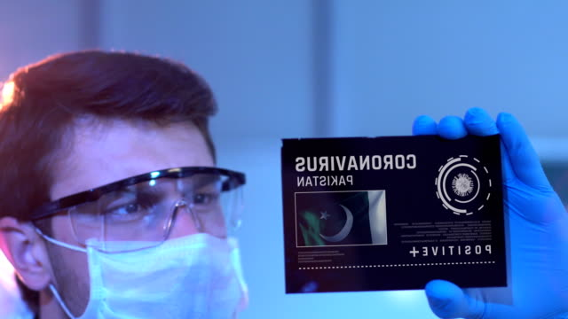 Researcher Looking at Coronavirus Results of Pakistan. Pakistani Flag on Digital Screen in Laboratory