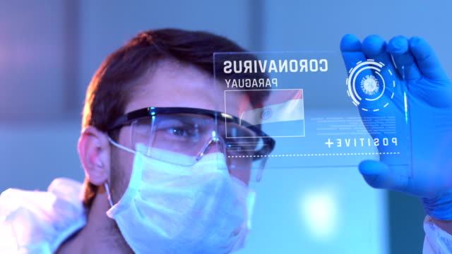 researcher looking at coronavirus results of paraguay. paraguayan flag on digital screen in laboratory - парагвай стоковые видео и кадры b-roll