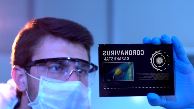 Researcher Looking at Coronavirus Results with Kazakh Flag on Digital Screen in Laboratory