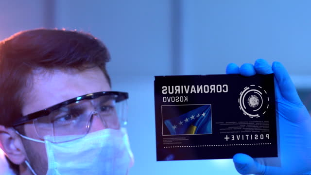 Researcher Looking at Coronavirus Results with Kosovo Flag on Digital Screen in Laboratory