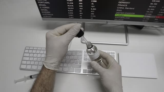 A researcher's hand checks a bottle of coronavirus or covid-19 vaccine