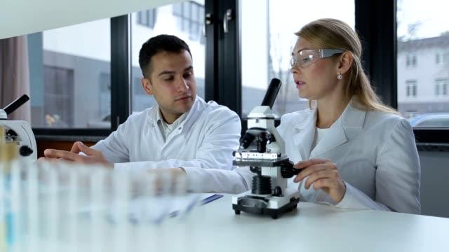 Researchers microscoping in biochemistry lab video