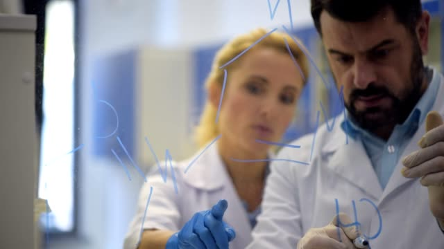Researches drawing chemical formulas on glass Always working together. Team of scientist standing next to each other and consulting while working together and writing down some chemical equations on a glass board. stem research stock videos & royalty-free footage